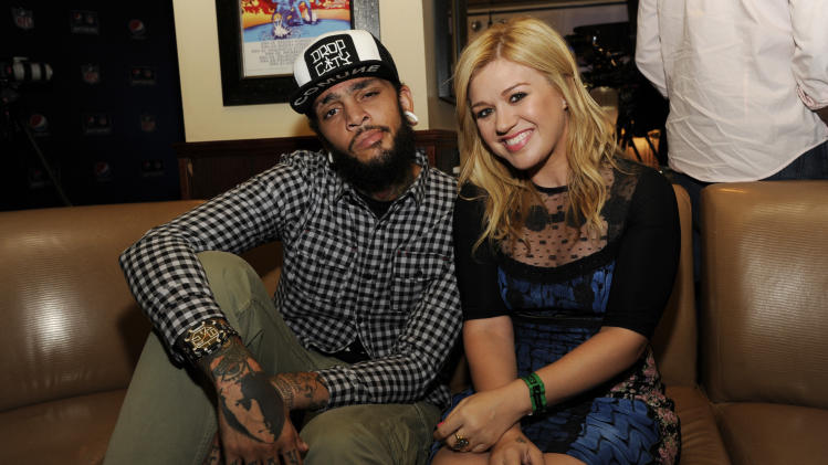 IMAGE DISTRIBUTED FOR PEPSI - From left, Pepsi NFL Anthems artists Travie McCoy and Kelly Clarkson catch up in the Blue Room at the Pepsi NFL Anthems Kickoff Eve on Tuesday Sept. 4, 2012, at Hard Rock Cafe in New York. (Photo by Evan Agostini/Invision for Pepsi/AP Images)