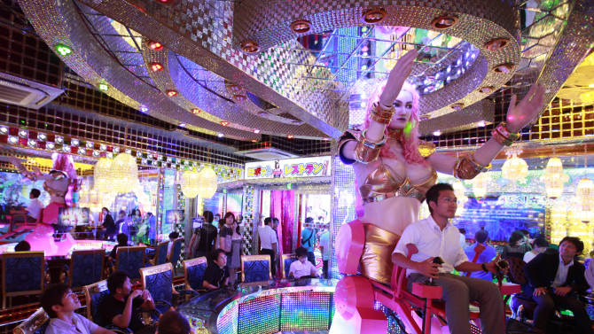 """A customer is seated on a 3.6 metre-high custom-made female robot at the newly opened """"Robot Restaurant"""" in Tokyo"""