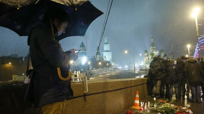 People gather near flowers and candles which were left at the place where Boris Nemtsov was shot dead, in central Moscow