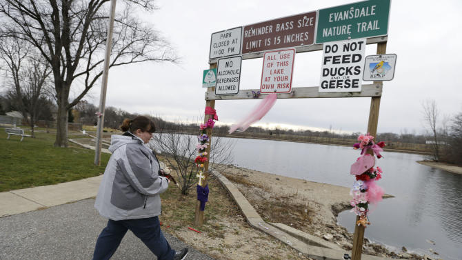 Tasha Gant, of Waterloo, Iowa, places a stuffed monkey at a memorial site at Meyers Lake Thursday, Dec. 6, 2012,  in Evansdale, Iowa where cousins Lyric Cook, 10, and Elizabeth Collins, 8, disappeared in July while riding their bikes,. Family members are waiting to hear whether the two bodies discovered by hunters on Wednesday are the two missing cousins. (AP Photo/Charlie Neibergall)