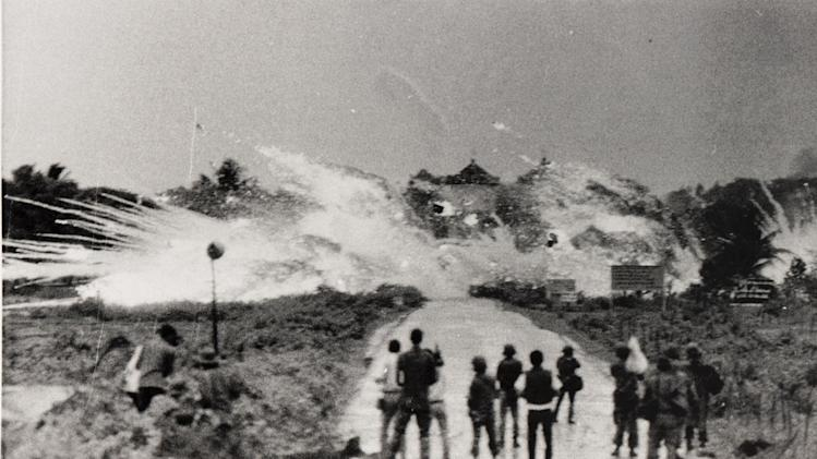 FILE - In this June 8, 1972 file photo, bombs with a mixture of napalm and white phosphorus jelly dropped by Vietnamese Air Force Skyraider bombers explode across Route 1, amidst homes and in front of the Cao Dai temple on the outskirts of Trang Bang, Vietnam. In the foreground are Vietnamese soldiers and journalists from various international news organizations. The towers of the Trang Bang Cao Dai temple are visible in the centre of the explosions. (AP Photo/Nick Ut)