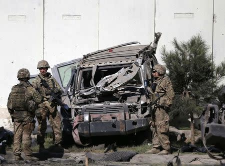 U.S. troops keep watch near a damaged vehicle at the site of suicide attack in Kabul
