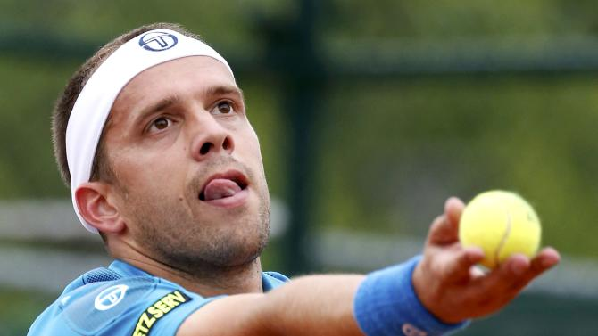 Gilles Muller of Luxembourg serves to Paolo Lorenzi of Italy during their men's singles match at the French Open tennis tournament at the Roland Garros stadium in Paris