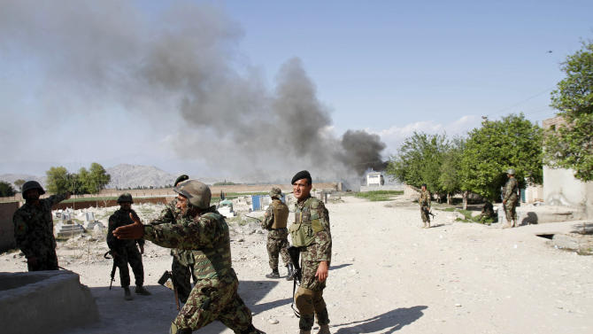 Afghan soldiers react after a suicide attack on the U.S.-led provincial reconstruction team (PRT) compound in the Behsood district of Jalalabad, east of Kabul Afghanistan, on Sunday, April 15, 15 2012. The Taliban launched a series of coordinated attacks on at least seven sites across the Afghan capital on Sunday, targeting NATO headquarters, the parliament and diplomatic residences. Militants also launched near-simultaneous assaults in three other eastern cities. (AP Phot/Rahmat Gul)
