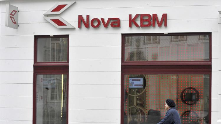 A woman walks next to a Nova KBM bank in Ljubljana