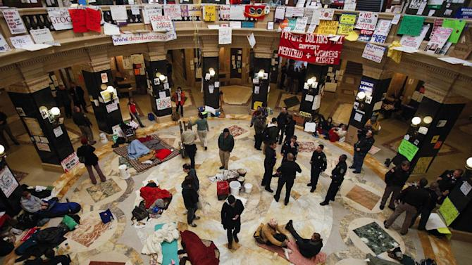 FILE - This Feb. 28, 2011 file photo shows protests continuing at the state Capitol in Madison, Wis., as police and demonstrators gather on the rotunda floor where opponents to the governor's bill to eliminate collective bargaining rights for many state workers have been sleeping. The nation's labor unions suffered sharp declines in membership last year, the Bureau of Labor Statistics said Wednesday, led by losses in the public sector as cash-strapped state and local governments laid off workers and _ in some cases _ limited collective bargaining rights.  (AP Photo/Andy Manis, File)
