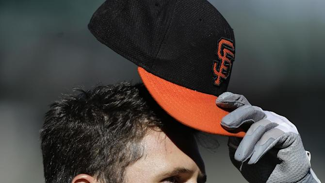 San Francisco Giants' Buster Posey removes his cap during batting practice before an exhibition spring training baseball game against the Oakland Athletics, Thursday, March 28, 2013, in San Francisco. (AP Photo/Ben Margot)