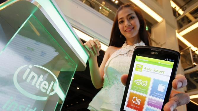 A model poses with an Acer Liquid C1 smartphone equipped with Intel Inside chips during a news conference in Bangkok