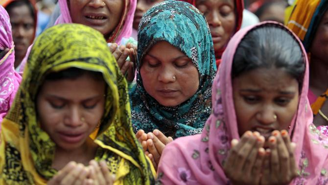 Bangladeshi women offer prayers for the souls of the 1,127 people who died in the garment building structure collapse last month, in Savar, Bangladesh, Tuesday, May 14, 2013. The Islamic prayer service was held a day after the army ended the nearly three-week, painstaking search for bodies among the rubble of the worst tragedy in the history of the global garment industry and turned control of the site over to the civilian government for cleanup. (AP Photo/A.M. Ahad)