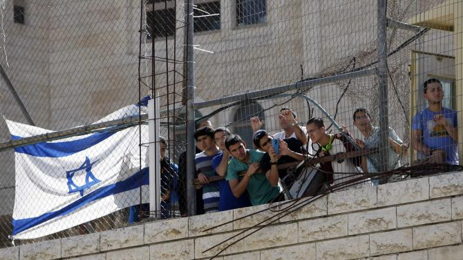 Israeli settlers watch a demonstration against the closure of Shuhada street to Palestinians, in the West Bank city of Hebron