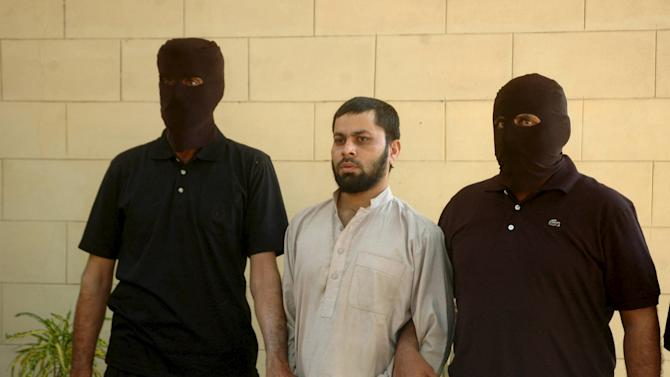 Security officials escort arrested terror suspect Sabir Khan, also known as Munna, in front of the media in Karachi