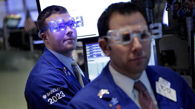 "Traders wear ""2013"" glasses as they work on the floor at the New York Stock Exchange in New York, Monday, Dec. 31, 2012.  The stock market struggled for direction Monday morning after five days of losses, with the ""fiscal cliff"" just hours away and lawmakers yet to reach a solution. (AP Photo/Seth Wenig)"