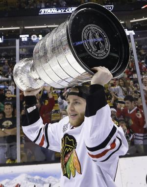 Chicago Blackhawks right wing Patrick Kane hoists the Stanley Cup after the Blackhawks beat the Boston Bruins 3-2 in Game 6 of the NHL hockey Stanley Cup Finals Monday, June 24, 2013, in Boston. (AP Photo/Elise Amendola)