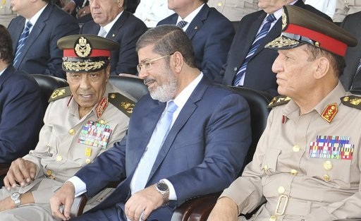 Egypt's new Islamist President Mohamed Mursi speaks with Field Marshal Hussein Tantawi and Egyptian Armed Forces Chief Of Staff Sami Anan during a soldier graduation ceremony at the Egyptian military academy in Cairo