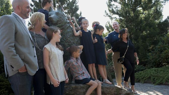 Retired Connecticut head coach Jim Calhoun, second from right, poses with his family at a Husky dog statue outside Gample Pavilion Storrs, Conn., Thursday, Sept. 13, 2012.  The 70-year-old Hall of Famer ran the men's program for 26 years and won three national titles, announced his retirement on Thursday. (AP Photo/Jessica Hill)