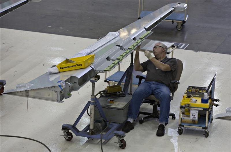 Workers assemble a wing flap for the Boeing 737-900 at their operations in Renton
