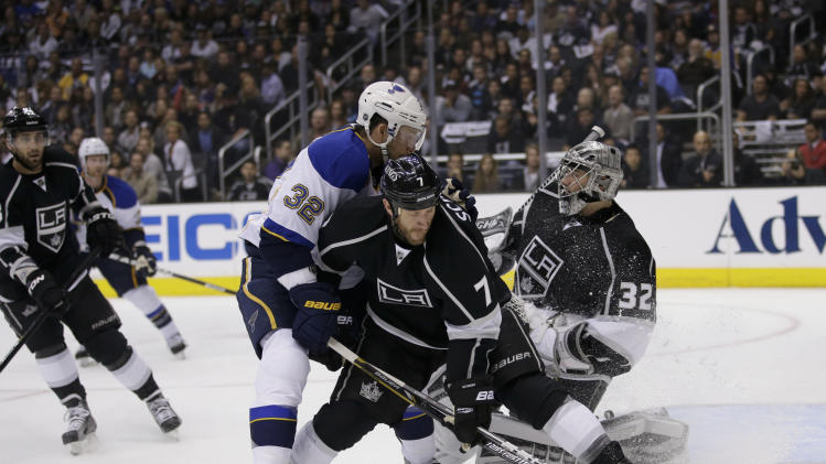 St. Louis Blues' Chris Porter(32) is defended by Los Angeles Kings' Rob Scuderi(7) as Los Angeles Kings goalie Jonathan Quick looks on during the first period in Game 3 of a first-round NHL hockey Stanley Cup playoff series n Los Angeles, Saturday, May 4, 2013. (AP Photo/Jae C. Hong)