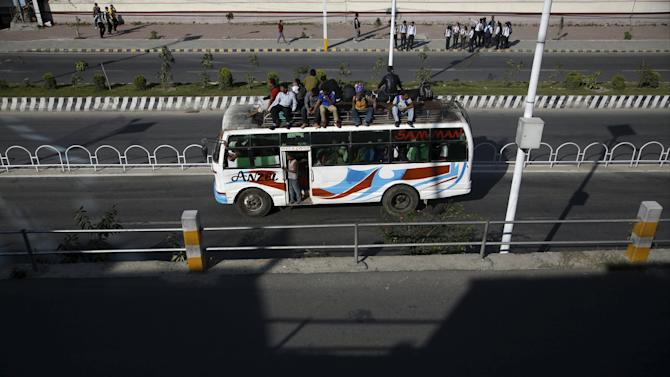 Passengers ride an overcrowded bus as limited public transportation operates in the city during the ongoing fuel crisis in Kathmandu