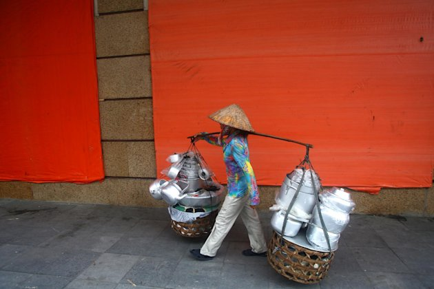In this photo taken Sunday, Sept. 9, 2012, a street vendor walks by the Trang Tien Plaza super mall which has been closed for a year for renovation in Hanoi, Vietnam. Once seen as an emerging Asian dynamo racing to catch up with its neighbors, Vietnam's economy is mired in malaise, dragged down by debt-hobbled banks, inefficient and corrupt state-owned enterprises and bouts of inflation. (AP Photo/Na Son Nguyen)