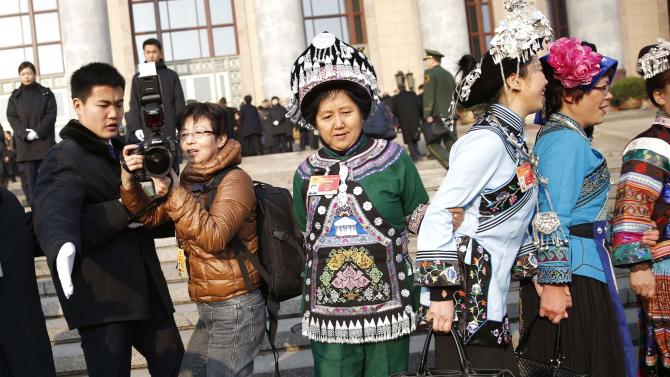 Ethnic minority delegates from Guizhou Province pose for pictures ahead of the opening of the annual full session of the National People's Congress, the country's parliament, in front of the Great Hall of the People at the Tiananmen Square, in Beijing