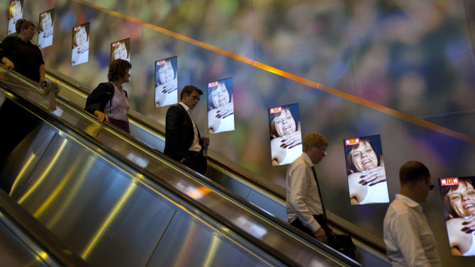 In this Tuesday, July 24, 2012 photo, Londoners observe electronic advertising by one of the Olympic sponsors, as they pass through an underground tube station, ahead of the 2012 Summer Olympics, in London. (AP Photo/Ben Curtis)