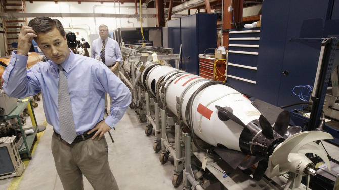 Christopher Del Mastro, head of anti submarine warfare mobil targets stands next to an unmanned underwater vehicle (UUV) in a lab at the Naval Undersea War Center in Middletown, RI., Tuesday, July 31, 2012.  Narragansett Bay is the testing ground for the Naval Undersea Warfare Center where the Navy is working toward its goal of achieving a squadron of self-driven, undersea vehicles.  (AP Photo/Stephan Savoia)