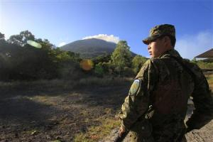 Soldier stands guard as the Chaparrastique volcano …