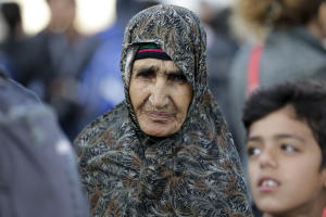 An elderly Afghan woman waits for a bus, transporting…