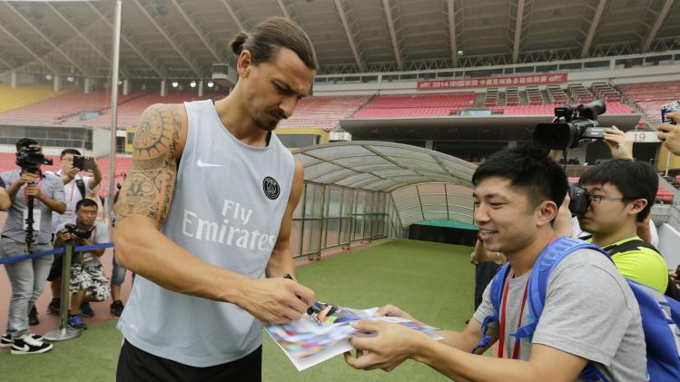 PSG's Ibrahimovic signs an autograph for a fan as he arrives for a training session in Beijing