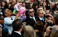 US President Barack Obama (L) picks up a baby while greeting supporters at a campaign rally in Nashua, New Hampshire. Obama, who made no changes in his campaign schedule, reviewed emergency preparations in a conference call with top domestic security and emergency assistance officials Saturday as he flew to New Hampshire, the White House said
