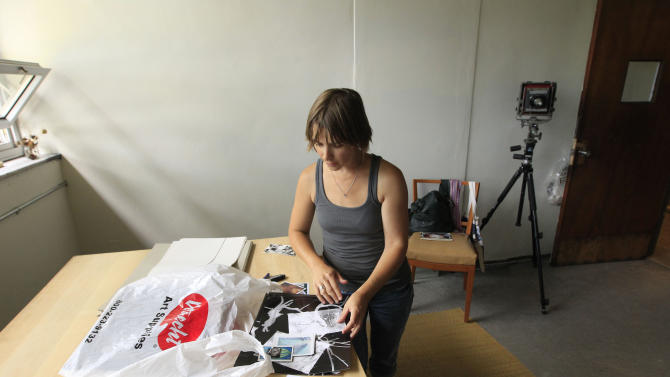 In a photo from July 24, 2012, photographer Elizabeth Sutton, 42,  sorts through some materials at 555 Nonprofit Gallery and Studio, housed in a former police station in Detroit.  Sutton, who is on the studio's board and an educator at the Detroit Institute of Arts, is converting space formerly used as detectives' offices into a darkroom. (AP Photo/Carlos Osorio)