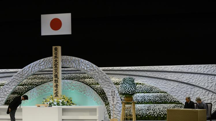 Japan's Prime Minister Shinzo Abe bows to Emperor Akihito and Empress Michiko in front of the altar for the victims of the March 11, 2011 earthquake and tsunami at the national memorial service in Tokyo