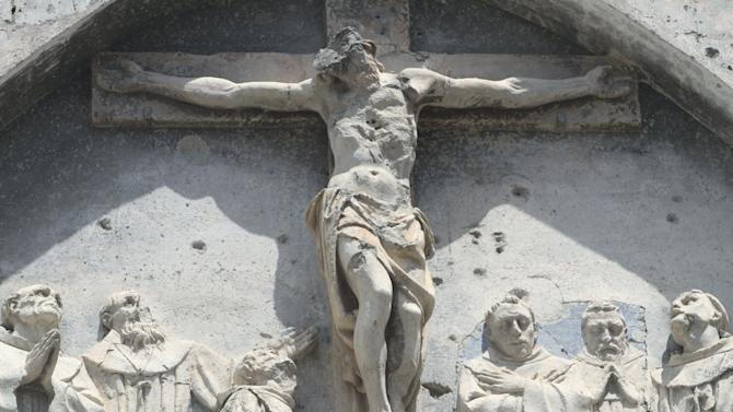 Bullet holes are seen on the destroyed relic of Christ on the Cross on the walls of the Catholic cathedral in Mogadishu