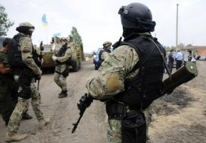 Ukrainian servicemen stand at the military camp near …