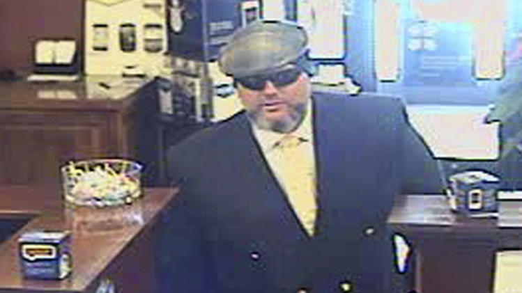 File-A file image provided by the Jackson, Wyo., Police Department shows Corey Donaldson, a 39-year-old Australian, during a bank robbery on New Year's Eve, 2012, at the U.S. Bank in Jackson, Wyo.  Donaldson is standing trial in Wyoming says he was justified in robbing a Jackson bank because he gave the money to the homeless.    (AP Photo/Jackson Police  Department,File)