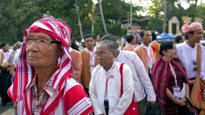 """A Karen ethnic minority representative of Aung San Suu Kyi's National League for Democracy, left, stands in a line to participate in first ever NLD party congress in Yangon, Myanmar, Friday, March 8, 2013. Nearly 900 representatives from across the country stood in neat lines outside the Taw Win (""""Royal Rose"""") restaurant, waiting to be screened for entry to elect their party leadership for the first time in the NLD's 25-year history. (AP Photo/Gemunu Amarasinghe)"""
