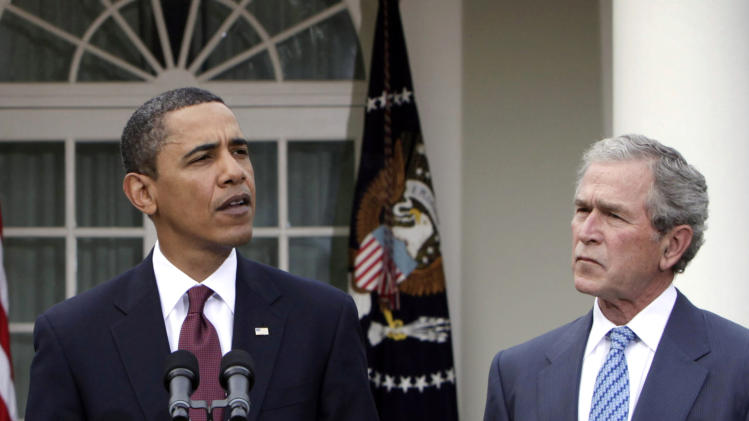 FILE - In this Jan. 16, 2010 file photo, former President George W. Bush listens as President Barack Obama speaks in the Rose Garden at the White House in Washington. President Barack Obama frequently blames President George W. Bush for America's shaky economy, high unemployment and foreign policy woes. But he's sure to change his tune on Thursday when Bush comes back to the White House in a rare limelight moment, The man who led the country for eight tumultuous years will have his portrait hung and Obama will be there applauding.  (AP Photo/Pablo Martinez Monsivais, File)