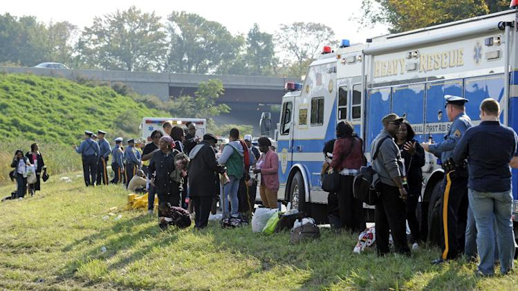 Passengers wait after their bus overturned in a ditch at an exit ramp off Route 80 in Wayne, N.J. Saturday, Oct. 6, 2012. The chartered tour bus from Toronto carrying about 60 people overturned on an interstate exit ramp. Three people have been taken to hospital with non-life-threatening injuries. (AP Photo/Bill Kostroun)