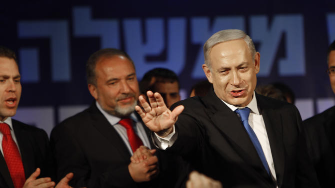 Israel's Prime Minister Benjamin Netanyahu, right, and former Foreign Minister Avigdor Lieberman greet their supporters  in Tel Aviv, Israel, Wednesday, Jan. 23, 2013.  According to exit polls Netanyahu's Likud Party emerged as the largest faction in a hotly contested parliamentary election on Tuesday, positioning the hard-liner to serve a new term as prime minister. (AP Photo/Oded Balilty)