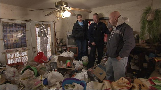 "Dr. Zasio Kieth and Dan stand on top of trash in the living room in the season premiere of ""Hoarders."""