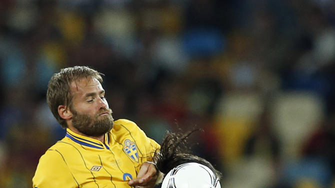England's Andy Carroll stops the ball in fromt of Sweden's Olof Mellberg  during the Euro 2012 soccer championship Group D match between Sweden and England in Kiev, Ukraine, Friday, June 15, 2012. (AP Photo/Sergei Grits)