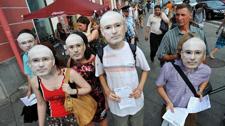 Wearing masks of Mikhail Khodorkovsky, opposition activists take part in a demonstration in St. Petersburg on June 26, 2013 to mark the jailed former tycoon's 50th birthday
