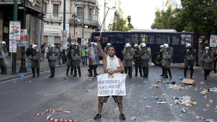 """A Muslim man holds a sign declaring """"USA your ridiculous film is an act of hatred of Islam"""", in front of a police cordon during a protest against a film produced in the U.S. that they say insults the Prophet Muhammad, in Athens, Sun. 23, 2012.  The protesters tried to march to the U.S. Embassy,  but riot police blocked all exits from the square and used tear gas to disperse the protesters. It is the first such protest against the film by Muslims in Greece.(AP Photo/Kostas Tsironis)"""