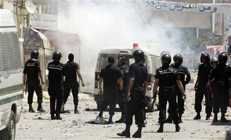 Riot police chase after protesters in the Tunisian capital Tunis