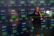 A television anchor stands in front of screens showing the start of trading in Facebook shares at the NASDAQ stock exchange. fell again in nervous trade on Friday and the euro hit a new four-month low against the dollar as ratings agencies further downgraded Greek and Spanish banks