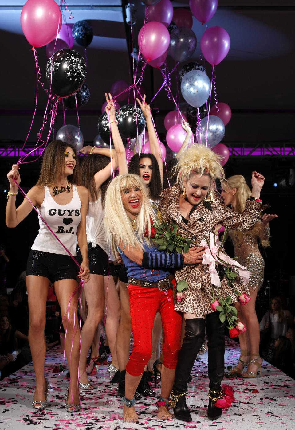 Designer Betsey Johnson, center, is joined on the runway by singer Cyndi Lauper, right, after the Betsey Johnson Spring 2013 collection show during Fashion Week, Tuesday, Sept. 11, 2012, in New York. (AP Photo/Jason DeCrow)