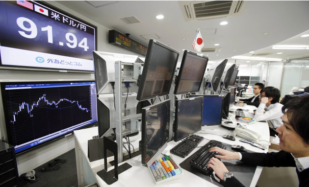 Currency traders work at a foreign exchange company in Tokyo,Tuesday, Feb. 26, 2013. In currency markets, the dollar was down 0.7 percent to 91.92 yen. But the yen, which has fallen by about 20 percen