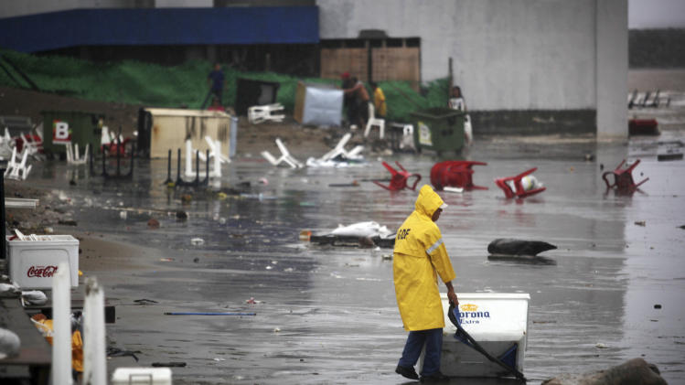 A vendor recovers a cooler after vendors were caught unprepared when high waves dragged their beach stalls into the sea in Veracruz, Mexico, Thursday, Aug. 9, 2012. Tropical Storm Ernesto headed into Mexico's southern Gulf coast as authorities in the flood-prone region prepared shelters, army troops and rescue personnel for drenching rains. (AP Photo/Felix Marquez)