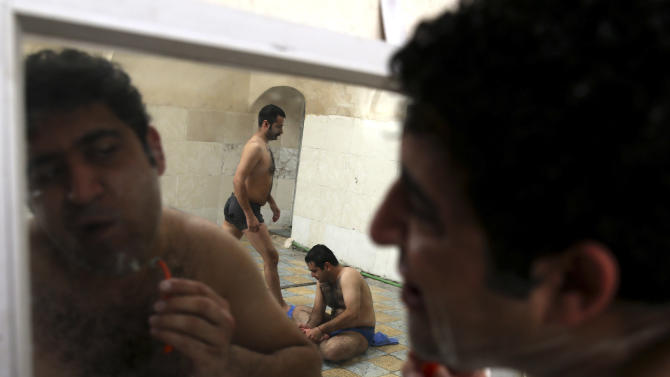 "In this Nov. 21, 2014 photo, a man shaves at the Setareh public bathhouse, in Yazd, Iran. The steamy air and curved tiled walls of Iran's famed public bathhouses, some rinsing and massaging patrons for hundreds of years, slowly may wash away as interest in them wanes. The bathhouses, known as ""hammams"" in Persian, find themselves in rough financial times as modern conveniences now allow showers and baths in most homes across the Islamic Republic. (AP Photo/Ebrahim Noroozi)"