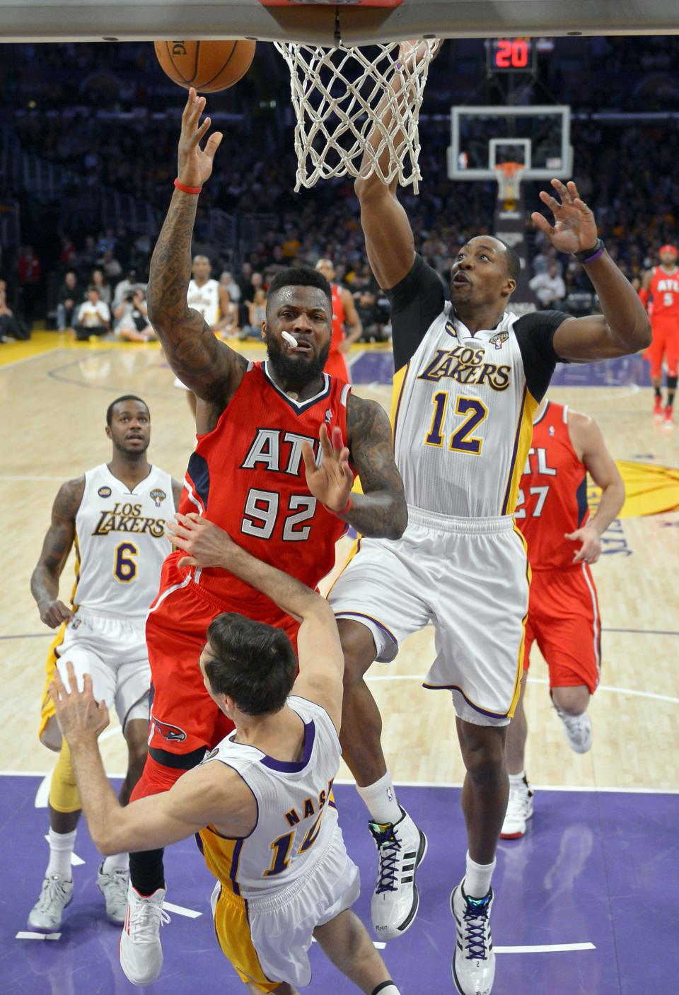 Atlanta Hawks forward DeShawn Stevenson, second from left, puts up a shot as he knocks over Los Angeles Lakers guard Steve Nash, below while center Dwight Howard, right, defends and forward Earl Clark looks on during the first half of their NBA basketball game, Sunday, March 3, 2013, in Los Angeles. (AP Photo/Mark J. Terrill)